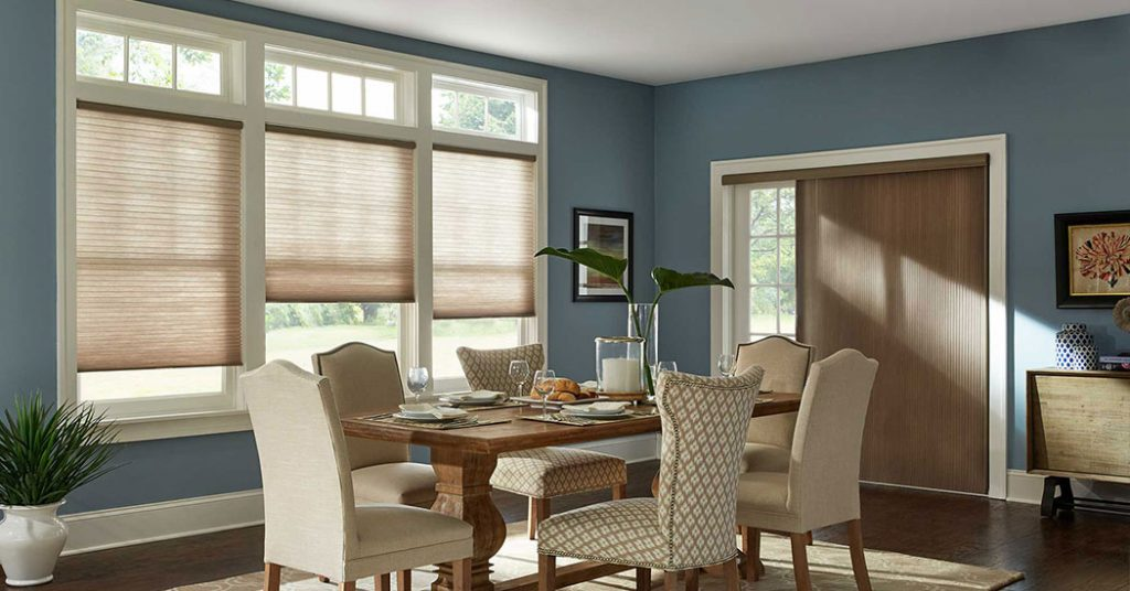 Beautiful muted and peaceful blue dining room with natural wood door, chair legs, and matching window shades.