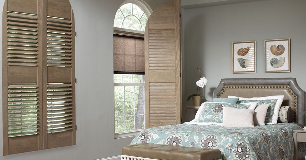 Greyish blue bedroom walls match a decorative duvet cover on a master bed with natural wood shutters over arched windows.