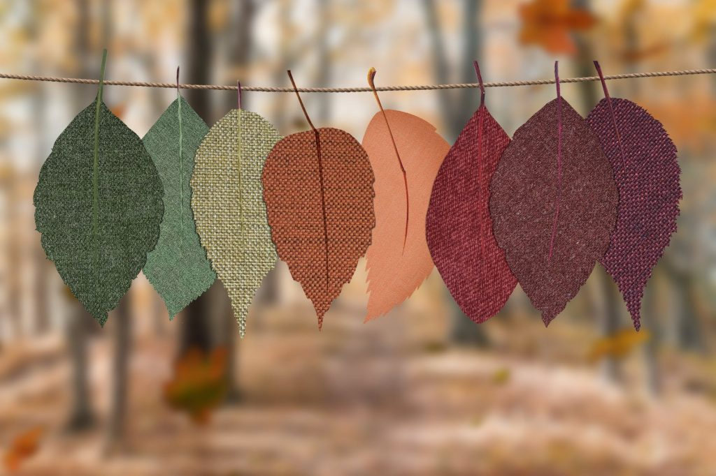 A garland of fall colored leaves made out of fabric hanging on a line of twine