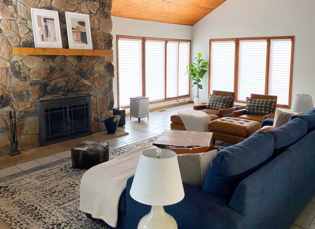 Motorized blinds over large windows in comfortable and rustic living room